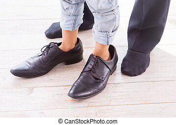 A little bit oversized. Close-up of child wearing large shoes while his father standing in socks near him
