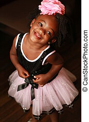 A little black girl smiling - A little black girl looking up...
