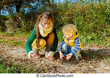 a little blond boy and his mom play outside