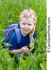 A little blond boy crouched in the green grass.