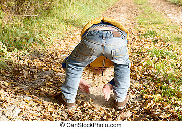 a little blond boy playing with dirt