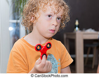 little blond boy playing with hand spinner - a little blond ...
