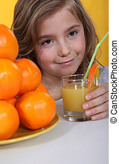 a little blonde girl drinking orange juice