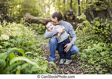 Little boy and his father on grass in autumn forest
