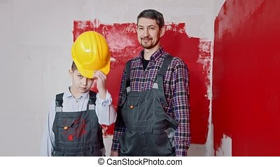 A little boy and his father painting walls - a boy puts on a helmet and holding a roller