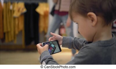 A little boy chooses clothes in the store and takes pictures of her on a smartphone