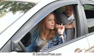 A little boy closes his mother's eyes while driving a car. Child indulges in car