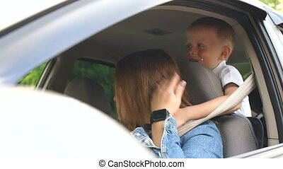 A little boy closes his mother's eyes while driving a car.
