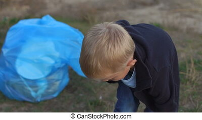 A little boy collects garbage on the beach by the river or lake in the Park.