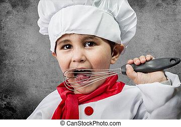 A little boy cook in uniform over vintage  background