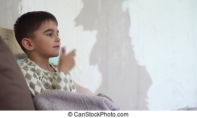 A little boy coughs for a cold and takes cover with a blanket