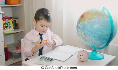 A little boy counts his savings on a calculator and writes in a notebook