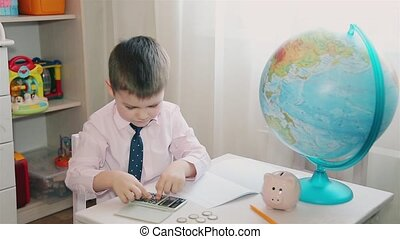 A little boy counts his savings on a calculator and writes in a notebook HD
