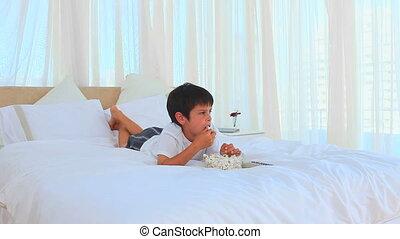A little boy eating popcorn