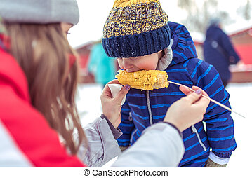 A little boy eats boiled corn in winter fair, on weekends in nature, blue warm jumpsuit, warm hat, mother feeds child, snack breakfast and lunch in nature winter. Vacation concept resort with child.
