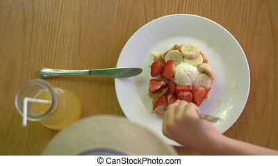 A little boy eats dessert Belgian waffles with strawberry and icecream in a cafe.