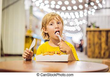 A little boy eats dessert waffles with jam in a cafe