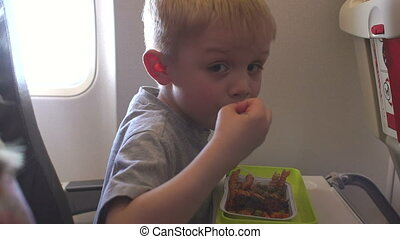 A little boy eats pasta with meat on the plane during the flight.
