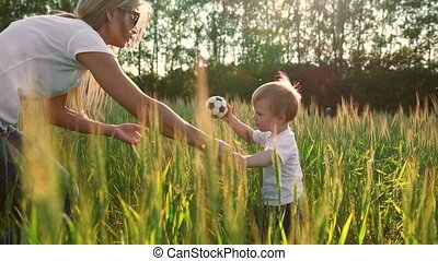 A little boy goes into a field with ears in the sunset light to meet his mother