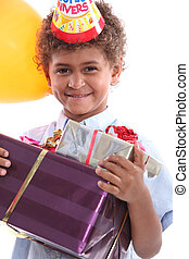 a little boy holding a conical hat and birthday gifts in his arms