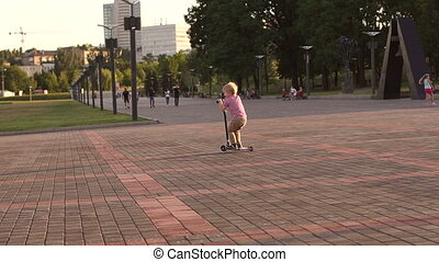A little boy in a red checkered shirt rides a scooter in a city Park at sunset.