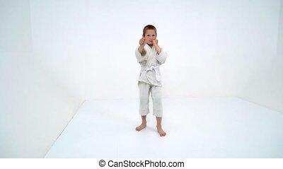 A little boy in a white kimono fulfills blows - A boy in a...