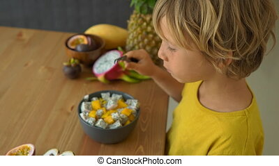 A little boy in a yellow shirt eats a mix of mango and...