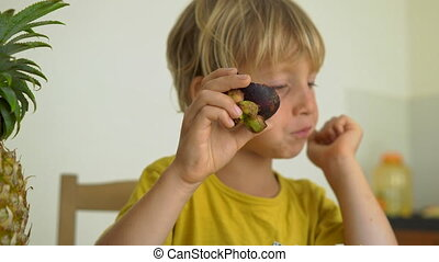 A little boy in a yellow shirt eats mangosteen. Lots of...