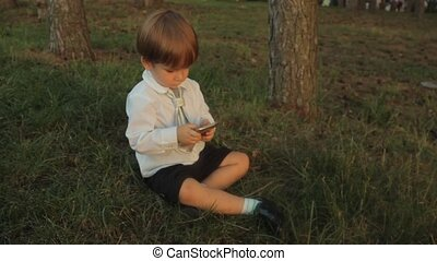 A little boy in black breeches, a white shirt with a tie, sitting on the green grass and playing with a smartphone in the park. Sunset in summer.