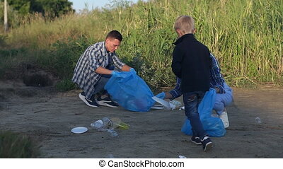 A little boy in gloves helps volunteers collect plastic garbage in the Park.