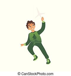 A little boy in green clothes runs with a toy windmill in his hands.