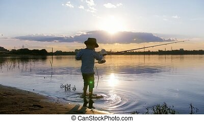 A little boy in panama hat holding a fishing rod - fishing...