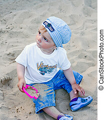 a little boy   in the sandbox
