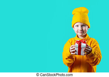a little boy in yellow hat and jacket holding a gift on a mint background
