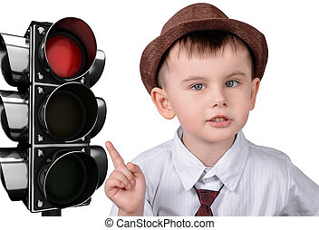 A little boy is pointing at a traffic light. The concept of traffic rules