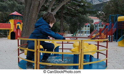 A little boy is riding a carousel in the playground.
