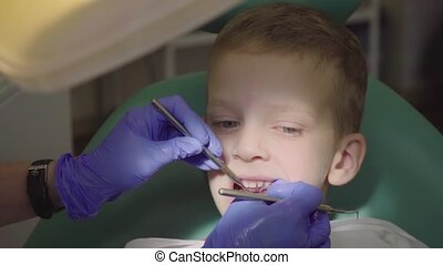 A little boy is sitting in the dentist's chair with his mouth open. The dentist checks the child's teeth