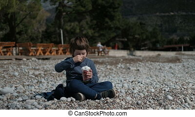 A little boy is sitting on the rocks and eats cream with pleasure.