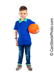 A little boy is standing with the ball under his arm