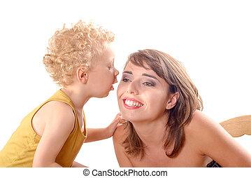 a little boy kissing a pretty girl