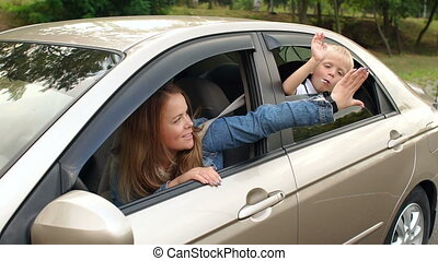 A little boy leaned out of the car window and claps his mother on the arm.