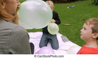 A little boy looks at the camera as his mom blows up his balloon - slowmo