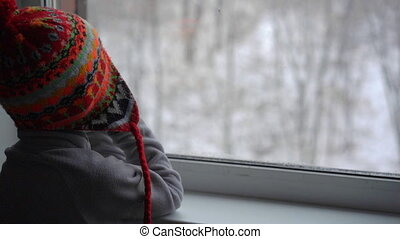 A little boy looks through the window on a heavy snowfall waiting for Christmas to come. Slowmotion shot