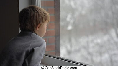 A little boy looks through the window on a heavy snowfall waiting for Christmas to come