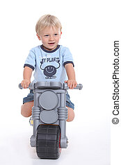 A little boy on his toy motorbike.