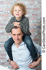 little boy on the shoulders of his father