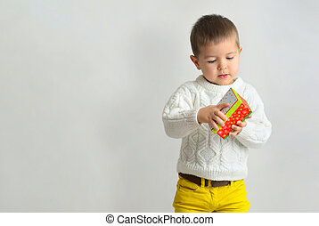 little boy opens a gift in a red box