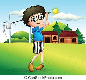 A little boy playing golf