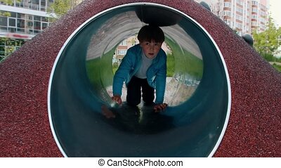 A little boy playing on the playground - crawling through the tube