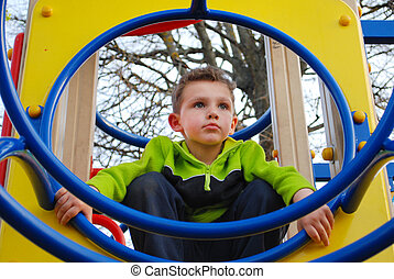 A little boy playing on the playground.
